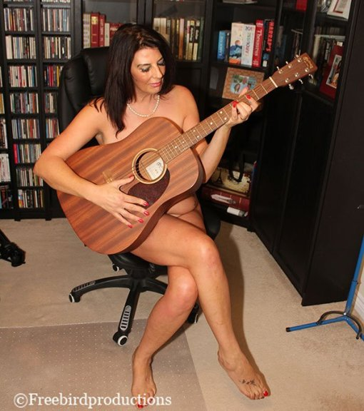 naked woman seated with guitar, in playing position
